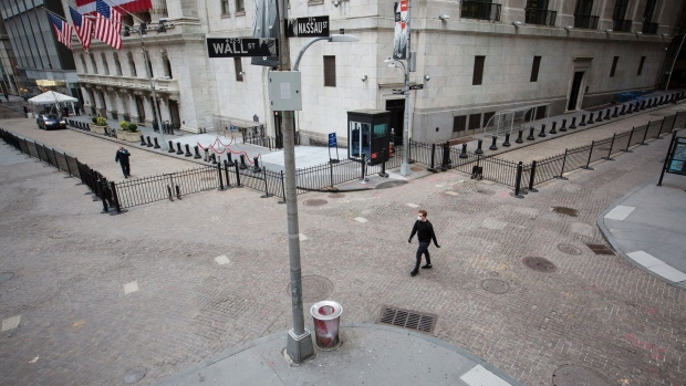 A pedestrian wearing a protective mask walks along Wall Street. Photographer: Michael Nagle/Bloomberg