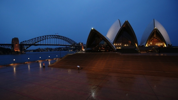 A pedestrian holding an umbrella walks along the Sydney Opera House forecourt during a partial lockdown imposed due to the coronavirus, at night in Sydney, Australia, on Friday, April 3, 2020. Australia's Prime Minister Scott Morrison said the government is close to announcing an agreement that will see rent relief for businesses hit by the coronavirus outbreak. The government wants a new industry code of practice for commercial tenancies, so any decline in revenue for a small- or medium-sized enterprise is reflected in a proportionate drop in rent they have to pay. Photographer: Brendon Thorne/Bloomberg