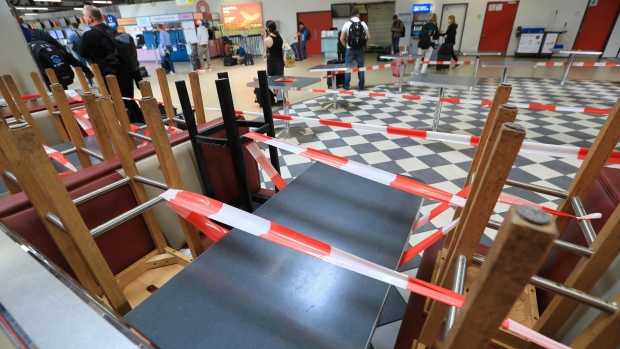 Security tape sits wrapped around upturned furniture in a closed dining area in Terminal C at Tegel airport, operated by Flughafen Berlin Brandenburg GmbH, in Berlin, Germany, on Tuesday, June 2, 2020. Berlin's Tegel airport can halt operations this month after the coronavirus virtually stopped traffic there, in what could spell the end for the Cold War-era facility. Photographer: Krisztian Bocsi/Bloomberg