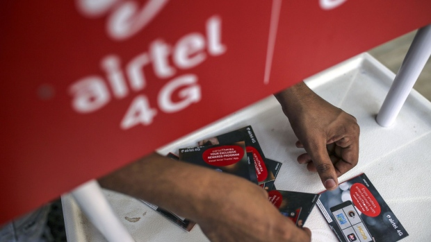 A vendor arranges Bharti Airtel Ltd. SIM card packets at a stall in Mumbai, India, on Sunday, Jan. 19, 2020. Telecom companies including Bharti and Vodafone Idea Ltd. have sought more time from India's top court to pay $13 billion in past dues as they plan to negotiate with the government, people with knowledge of the matter said. Photographer: Dhiraj Singh/Bloomberg