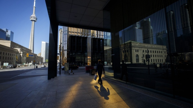 A pedestrian walks on the sidewalk in the financial district of Toronto, Ontario, Canada, on Friday, May 22