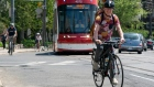 Cyclists ride up a hill with a TTC streetcar in Toronto
