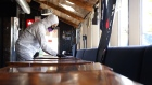 A worker disinfects tables inside a bar in Toronto, Ontario