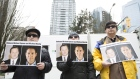 Protesters hold photos of Canadians Michael Spavor and Michael Kovrig