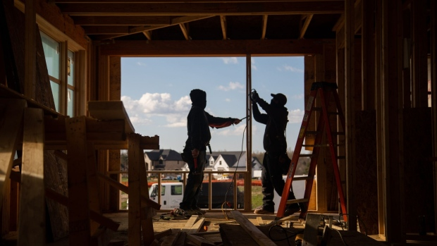 Construction workers install frames for windows and doors in a home being built in Michigan. Photographer: Emily Elconin/Bloomberg