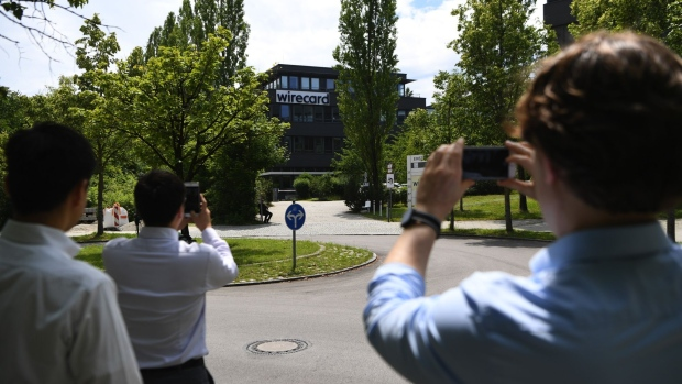 Pedestrians stop to take smartphone photographs of the Wirecard AG headquarters in Munich, Germany, on Thursday, June 25, 2020. Wirecard filed for insolvency, following the arrest of its CEO amid a massive accounting scandal that left the German payment-processing firm scrambling to find over $2 billion dollars missing from its balance sheet.