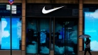 A pedestrian passes in front of a closed Nike store. Photographer: Demetrius Freeman/Bloomberg