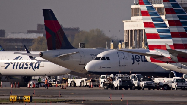 A JetBlue Airways Corp. plane taxis next to American Airlines Group Inc., Delta Air Lines Inc., and Alaska Airlines Inc. aircraft at Reagan National Airport (DCA) in Arlington, Virginia, U.S., on Monday, April 6, 2020. U.S. airlines are applying for federal aid to shore up their finances as passengers stay home amid the coronavirus pandemic. Photographer: Andrew Harrer/Bloomberg