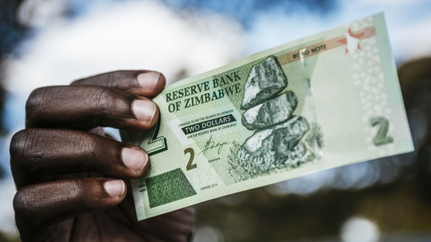 A man holds a Zimbabwean two dollar bond banknote for an arranged photograph in Harare, Zimbabwe, on Tuesday, July 31, 2018. Zimbabwe's main opposition party said it was well ahead in the first election of the post-Robert Mugabe era and it's ready to form the next government, as unofficial results began streaming in. Photographer: Waldo Swiegers/Bloomberg