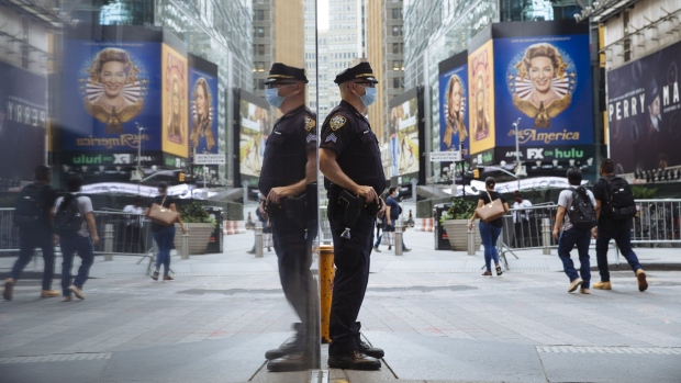 An NYPD officer wearing a protective mask stands in Times Square. Bloomberg/Angus Mordant