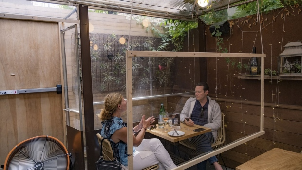 Customers have lunch at a restaurant behind a protective barrier in Hoboken, New Jersey, on June 15, 2020. Photographer: Jeenah Moon/Getty Images North America