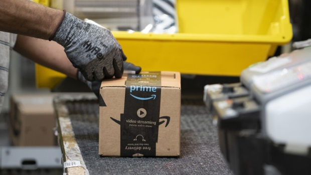 An employees places a label on a box at the Amazon.com Inc. fulfillment center in Baltimore, Maryland, U.S., on Tuesday, April 30, 2019. Amazon.com will spend $800 million in the current quarter to reduce delivery times for top customers to one day from two, trying to revive its main e-commerce franchise and ward off greater competition. Photographer: Melissa Lyttle/Bloomberg