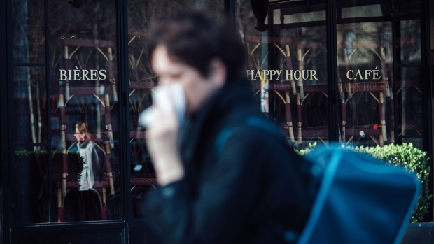 A pedestrian walks by a closed cafe restaurant as it advertises a 'Happy Hour' sales promotion in Paris, France, on Sunday, March 15, 2020. France closed restaurants, cafés and non-essential stores and Spain imposed a national lockdown as European governments from Scandinavia to the Balkans increasingly curtailed public life to fight the coronavirus. Photographer: Cyril Marcilhacy/Bloomberg