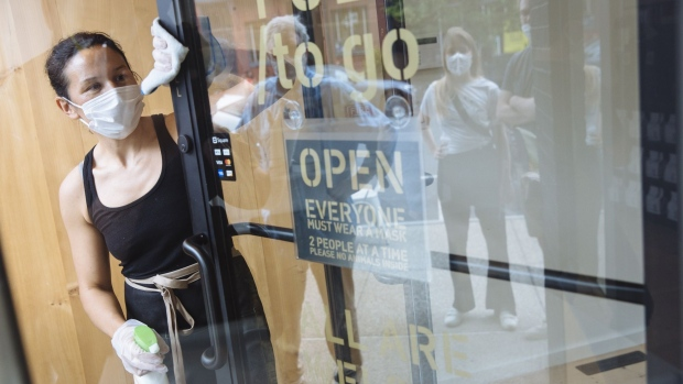 "People wearing protective masks are reflected in the window as a worker disinfects the door to prevent the spread of Covid-19 in Hudson, New York, U.S., on Sunday, June 28, 2020. As part of the phase 3 of reopening, the city of Hudson has implemented a ""Shared Summer Streets"" program that will allow businesses and pedestrians the space needed to operate with social distancing."