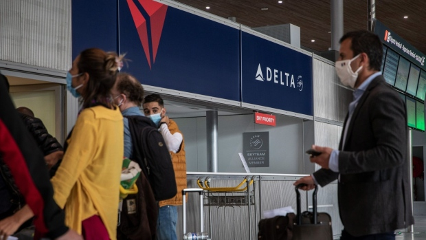 Travelers wearing protective face masks queue at a Delta customer service desk. Photographer: Adrienne Surprenant/Bloomberg