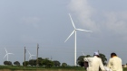 Wind turbines manufactured by Inox Wind Ltd. operate near electricity pylons at the Ostro Energy Pvt. Lahori Wind Farm in Lahori, Madhya Pradesh, India, on Monday, Aug. 14, 2017. As of June, India had 32 gigawatts of wind capacity. The nation is aiming to raise that to 60 gigawatts by 2022 as part of the country's climate pledge. Photographer: Dhiraj Singh/Bloomberg