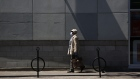 A pedestrian wearing a protective mask walks down Bank St. in Ottawa, Ontario, Canada, on Wednesday,