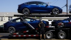 Workers unload Tesla Model 3 electric vehicles from a car carrier outside the company's delivery center in Marina Del Rey, California.
