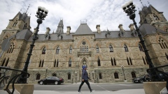 A pedestrian wearing a protective mask walks past the entrance of West Block on Parliament Hill in Ottawa, Ontario, Canada, on Wednesday, April 29, 2020.