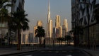 "The Burj Khalifa skyscraper, center, stands beyond an empty road among other office buildings on the city skyline seen from Dubai Design District in Dubai, United Arab Emirates, on Tuesday, June 9, 2020. ""An exodus of middle class residents could create a death spiral for the economy,"" said Ryan Bohl, a Middle East analyst at Stratfor."" Photographer: Christopher Pike/Bloomberg"