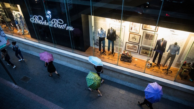 Pedestrians holding umbrellas walk past a Brooks Brothers store at the Gaysorn Village shopping mall in Bangkok. Photographer: Taylor Weidman/Bloomberg