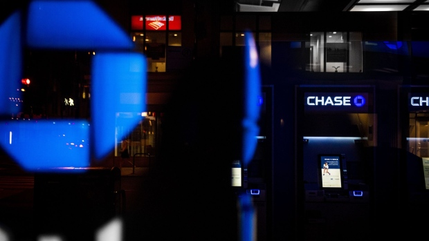 JPMorgan Chase & Co. signage is illuminated at night at a bank branch in Chicago, Illinois, U.S., on Tuesday, July 10, 2017. JPMorgan Chase & Co. is scheduled to release earnings figures on July 13. Photographer: Christopher Dilts/Bloomberg