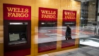 A person wearing a protective mask is reflected in the window of a temporarily closed Wells Fargo & Co. Bank branch in New York, U.S., on Friday, April 10, 2020. Wells Fargo is scheduled to release earnings figures on April 14.