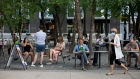 A woman walks by wearing a mask as people are seen at outdoor seating in Yorkville