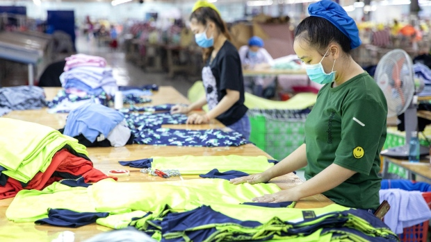 Workers fold clothing at a Thai Son S.P. Co. garment factory in Binh Thuan province, Vietnam, on Friday, Oct. 11, 2019. Vietnam's economic expansion this year may exceed the higher end of an official estimate, President Nguyen Phu Trong said. Growth may be more than 6.8%, and gross domestic product may surpass $266 billion, Trong said in a government statement on Oct. 13.