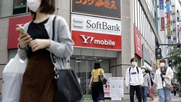 Pedestrians wearing protective masks cross a road in front of a SoftBank Corp. store in Tokyo, Japan, on Friday, May 15, 2020. SoftBank Group Corp. expects to book a record 1.35 trillion yen ($12.5 billion) operating loss for the fiscal year ended March 31 when it reports results on Monday.