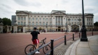A cyclist takes a photograph of Buckingham Palace in London, U.K., on Friday, July 3, 2020. As the U.K. prepares to reopen pubs, restaurants and hotels on July 4, the government and businesses are counting on the economy getting a big boost on the path to recovery. Photographer: Chris Ratcliffe/Bloomberg