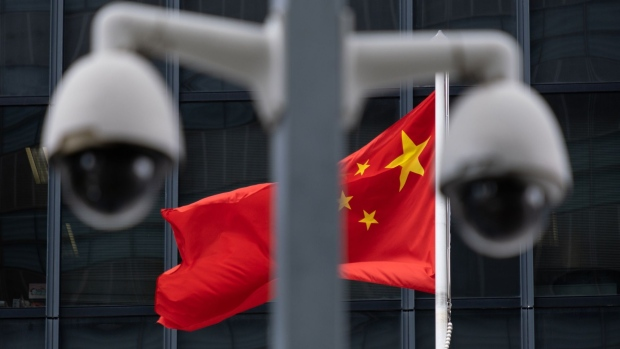 The flag of China is flown behind a pair of surveillance cameras outside the Central Government Offices in Hong Kong, China, on Tuesday, July 7, 2020. Hong Kong leader Carrie Lam defended national security legislation imposed on the city by China last week, hours after her government asserted broad new police powers, including warrant-less searches, online surveillance and property seizures. Photographer: Roy Liu/Bloomberg