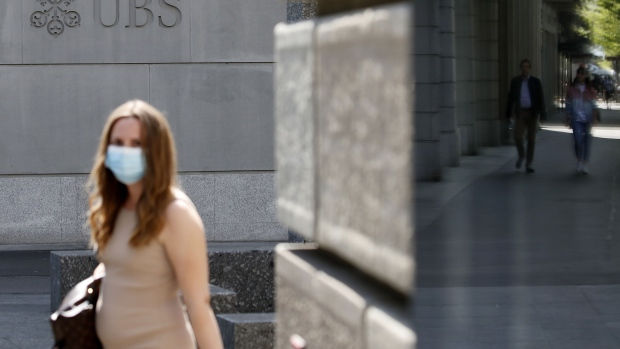 A pedestrian wearing a protective face mask walks past the UBS Group AG headquarters in Zurich, Switzerland, on Friday, April 17, 2020. A UBS appeal of a record 4.5 billion-euro ($4.9 billion) French fine for helping clients stash undeclared funds in offshore accounts was postponed over concerns related to coronavirus pandemic, according to people familiar with the case. Photographer: Angel Garcia/Bloomberg
