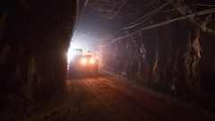A truck moves through a tunnel to pick up rock ore from the digging floor at the underground gold mine.