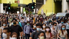 Pedestrians wearing protective masks walk across a road in Hong Kong, China, on Friday, July 10, 2020.