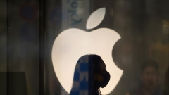 A employee wearing a protective mask is silhouetted while standing in front of an Apple Inc. logo at the company's store, temporarily closed due to the coronavirus, in the Ginza area of Tokyo, Japan, on Sunday, March 15, 2020.