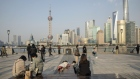 People wearing protective masks walk along the Bund. Bloomberg/Qilai Shen