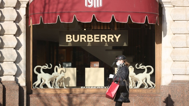 A shopper wearing a protective face mask walks past a Burberry Group Plc luxury fashion store in Moscow, Russia, on Thursday, March 26, 2020. With the extent of Russia's coronavirus epidemic distorted by a lack of testing, Moscow Mayor Sergey Sobyanin ordered restaurants and most stores in Europe's biggest city to shut down for a week.