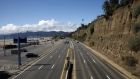 Vehicles drive in light traffic along Pacific Coast Highway north of the Santa Monica Pier, temporarily closed due to the coronavirus, in Santa Monica, California on March 19.