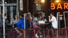 People sit outside a bar in the East Village neighborhood of New York on July 6, 2020.