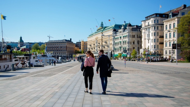 Pedestrians walk near the habour in Stockholm, Sweden, on Friday, May 22, 2020. Sweden, which has refused to close down schools and restaurants to contain the new coronavirus, is being closely watched as many other countries are gradually opening up their economies from stricter lockdowns. Photographer: Loulou D'Aki/Bloomberg