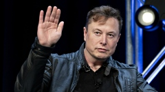 Elon Musk, founder of SpaceX and chief executive officer of Tesla Inc., waves while arriving to a discussion at the Satellite 2020 Conference in Washington, D.C., U.S., on Monday, March 9, 2020. The event comprises important topics facing both satellite industry and end-users, and brings together a diverse group of thought leaders to share their knowledge.