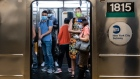Commuters wearing protective masks stand inside a subwaytrain in New York. Photographer: Jeenah Moon/Bloomberg