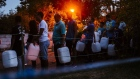 Residents queue to fill plastic water bottles and containers as night falls at the Newlands natural water spring in Cape Town in 2018.