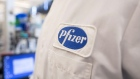 The Pfizer logo on the lab coat of an employee at the company's research and development facility in Cambridge, Massachusetts.