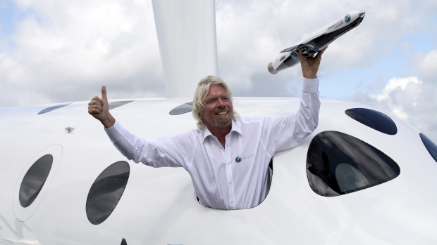 Richard Branson with a model of the LauncherOne rocket from the window of Virgin Galactic's SpaceShipTwo at the Farnborough International Air Show in the U.K. in 2012. Photographer: Bloomberg