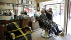 A barber wearing a protective mask cuts a customer's hair at a barber shop in Ottawa, Ontario, Canada, on Friday, June 12, 2020.