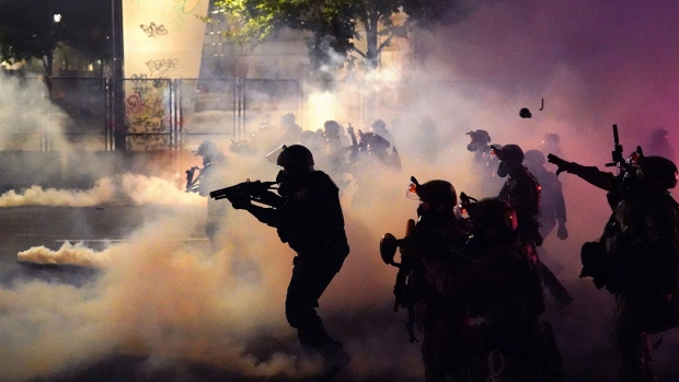 Federal officers deploy tear gas and munitions while dispersing a crowd in Portland on July 24. Photographer: Nathan Howard/Getty Images