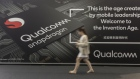 An attendee walks past an advertisement for Qualcomm at the MWC Shanghai exhibition.