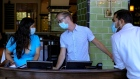 Employees wearing protective masks talk at a restaurant in Chicago, Illinois, U.S.